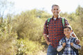 Father and son hiking in countryside wearing backpacks smiling to camera Royalty Free Stock Image
