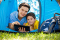 Father and son on a hiking trip portrait of young his using tablet computer during camping smiling Royalty Free Stock Photo