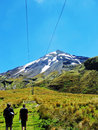 Father son hiking up track to snowy mountain nz a mature and his young adult start off their trekking adventure by the foothilss Royalty Free Stock Photography