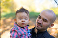 Father and son holding baby at a park in the autumn Royalty Free Stock Photo
