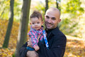 Father and son holding baby at a park in the autumn Royalty Free Stock Photography