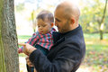 Father and son holding baby at a park in the autumn Stock Photography