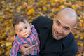 Father and son holding baby at a park in the autumn Stock Photos