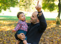 Father and son holding baby at a park in the autumn Stock Image
