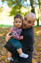 Father and son holding baby at a park in the autumn Stock Photo