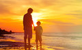 Father and son holding hands at sunset sea Royalty Free Stock Photo