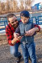 Father and son holding remote control joystick and piloting quadrocopter Royalty Free Stock Photo