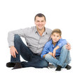Father and son hugging her sitting on the floor studio photo on white background Stock Photography