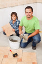 Father and son laying floor tiles together ceramic in a new home Stock Photo