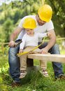 Father and son little helping his with building work Stock Photos