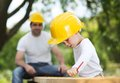 Father and son little helping his with building work Stock Photography