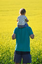 Father and son looking on rapeseed field on summer day little yellow flowers background Stock Photos