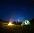 Father and son near campfire and tent under night sky Royalty Free Stock Photo
