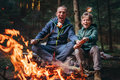 Father and son overroast their marshmallow candies on the campfire Royalty Free Stock Photo