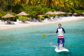 Father and son paddling on stand up board having fun during summer beach vacation Royalty Free Stock Photos