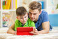 Father and son play with tablet computer at home Royalty Free Stock Photo