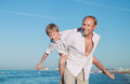 Father with son play together on the sea side Royalty Free Stock Photo