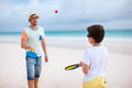 Father and son playing beach tennis Royalty Free Stock Photo