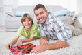 Father and son playing checker game on fur portrait of happy while lying at home Stock Photos