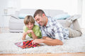 Father and son playing checker game while lying on fur happy at home Royalty Free Stock Photo