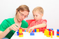 Father and son playing with colorful blocks at home Stock Images