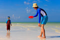 Father and son playing with flying disc at the tropical beach Royalty Free Stock Photography
