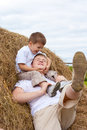 Father and son playing in haystack together Royalty Free Stock Photography
