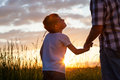 Father and son playing at the park at the sunset time. Royalty Free Stock Photo