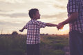 Father and son playing in the park at the sunset time. Royalty Free Stock Photo