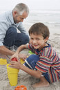Father and son playing with sand portrait of cute little boy at beach Royalty Free Stock Image