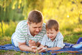 Father and son playing with smartphone together outdoors Stock Image