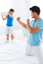 Father and son playing together with pillows. Royalty Free Stock Photo