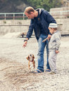 Father and son playing wirh little puppy on the seaside Royalty Free Stock Photo