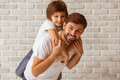 Father and son portrait of a handsome carrying his cute on back both in white t shirts smiling standing against white brick wall Royalty Free Stock Image