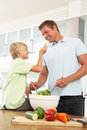 Father & Son Preparing Salad In Modern Kitchen Stock Photos
