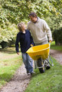 Father and son pushing wheelbarrow Stock Image