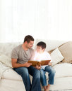 Father and son reading a fairy tale in the living room Stock Photography