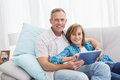 Father with son relaxing on the couch using laptop Royalty Free Stock Photo