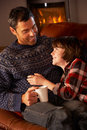 Father And Son Relaxing With Hot Drink Stock Images