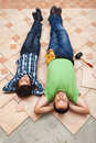 Father and son resting while laying floor tiling ceramic tiles Royalty Free Stock Images