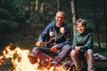 Father and son roast marshmallow candies on the campfire in fore Royalty Free Stock Photo