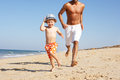 Father And Son Running Along Beach Royalty Free Stock Photos