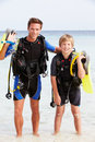 Father and son with scuba diving equipment on beach holiday smiling to camera Royalty Free Stock Photos
