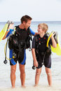Father and son with scuba diving equipment on beach holiday smiling to camera Stock Image