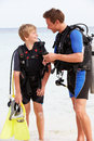Father and son with scuba diving equipment on beach holiday smiling to each other Stock Photos