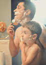 Father and son shaving in the bathroom a is teaching his how to shave wiping cream on his face Stock Photo