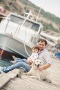 Father and son sits with dogs on a bench near the sea happy young big dog sitting against yachts Royalty Free Stock Image