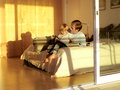 Father and son sitting on bed looking at photo album view through open sliding doors Royalty Free Stock Image