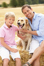 Father And Son Sitting With Dog On Straw Bales In Royalty Free Stock Photos
