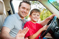 Father and son is sitting at the stearing wheel smiling camera Royalty Free Stock Photo